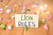 Conceptual hand writing showing Lion Rules. Business photo text epitome of strength power and masculinity Master of own domain Colored crumpled papers wooden floor background clothespin.