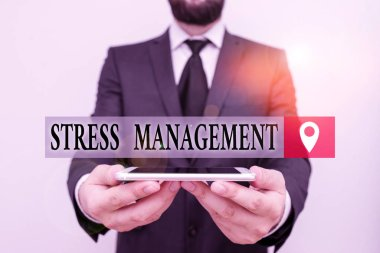 Conceptual hand writing showing Stress Management. Business photo text learning ways of behaving and thinking that reduce stress Male human wear formal work suit hold smartphone using hand.