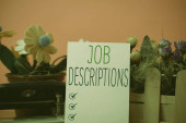 Writing note showing Job Descriptions. Business photo showcasing a formal account of an employee s is responsibilities Flowers and writing equipments plus plain sheet above textured backdrop.