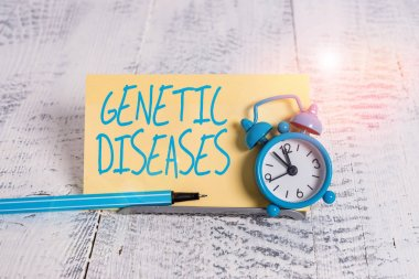 Handwriting text Genetic Diseases. Concept meaning disease caused by an abnormality in an individual s is genome Mini blue alarm clock stand tilted above buffer wire in front of notepaper.