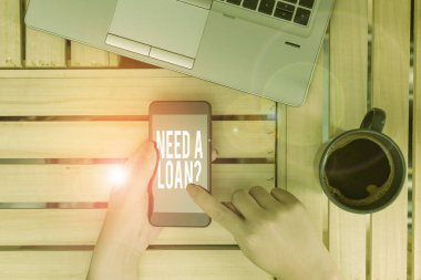 Text sign showing Need A Loan Question. Conceptual photo asking he need money expected paid back with interest woman computer smartphone drink mug office supplies technological devices.