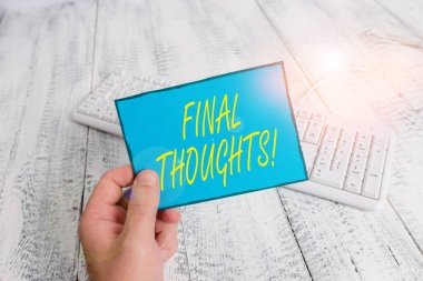 Writing note showing Final Thoughts. Business photo showcasing should be last few sentences within your conclusions Man holding colorful reminder square shaped paper wood floor.