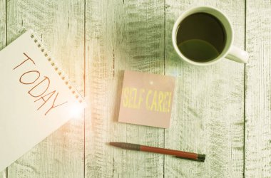 Writing note showing Self Care. Business photo showcasing practice of taking action to preserve or improve ones own health Stationary placed next to a cup of black coffee above the wooden table.