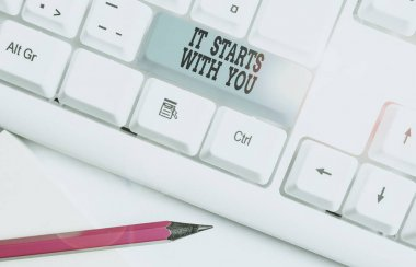 Text sign showing It Starts With You. Conceptual photo Motivation for starting doing something Have discipline White pc keyboard with empty note paper above white background key copy space.