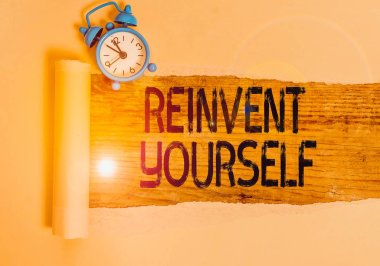 Text sign showing Reinvent Yourself. Conceptual photo to do something differently from before Change behavior Alarm clock and torn cardboard placed above a wooden classic table backdrop.