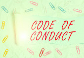 Text sign showing Code Of Conduct. Business photo text Ethics rules moral codes ethical principles values respect Paper clip and torn cardboard placed above a plain pastel table backdrop