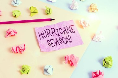 Writing note showing Hurricane Season. Business concept for time when most tropical cyclones are expected to develop Colored crumpled papers empty reminder blue yellow clothespin