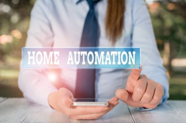 Handwriting text Home Automation. Concept meaning home solution that enables automating the bulk of electronic Female business person sitting by table and holding mobile phone.