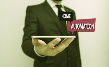 Writing note showing Home Automation. Business concept for home solution that enables automating the bulk of electronic Male human wear formal work suit hold smartphone using hand