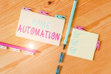 Text sign showing Home Automation. Business photo showcasing home solution that enables automating the bulk of electronic Colored clothespin papers empty reminder wooden floor background office