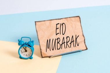 Conceptual hand writing showing Eid Mubarak. Concept meaning traditional Muslim greeting reserved for the holy festivals Alarm clock beside a Paper sheet placed on pastel backdrop stock vector
