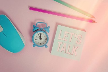 Text sign showing Let S Talk. Conceptual photo they are suggesting beginning conversation on specific topic Alarm clock wakeup blank notepad mouse markers colored background.