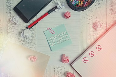 Conceptual hand writing showing Update. Business photo showcasing by adding new information or making corrections Up to date Smartphone sheet clips pen paper balls envelope wooden back.