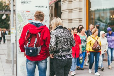 Moscow, Russia - JULY 7, 2017. A man in a bright red jacket, backpack Adidas and blue jeans with a woman standing and looking at a map of the city. Against the background of a multicolored crowd of