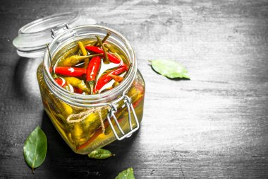 Pickled hot chili peppers in glass jar.