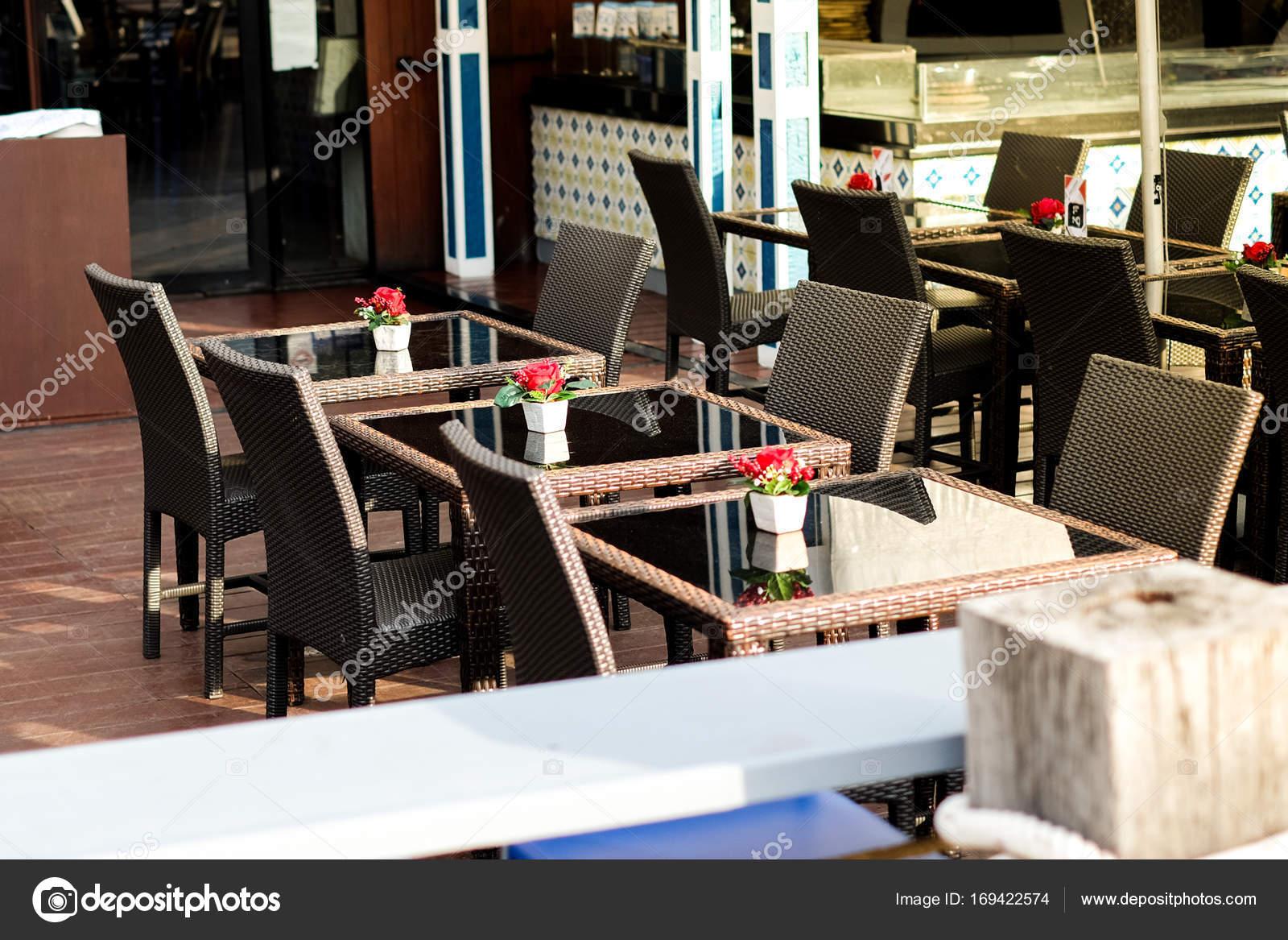 Muchas sillas de mimbre negro con rojo color de rosa en Jarrón y ...