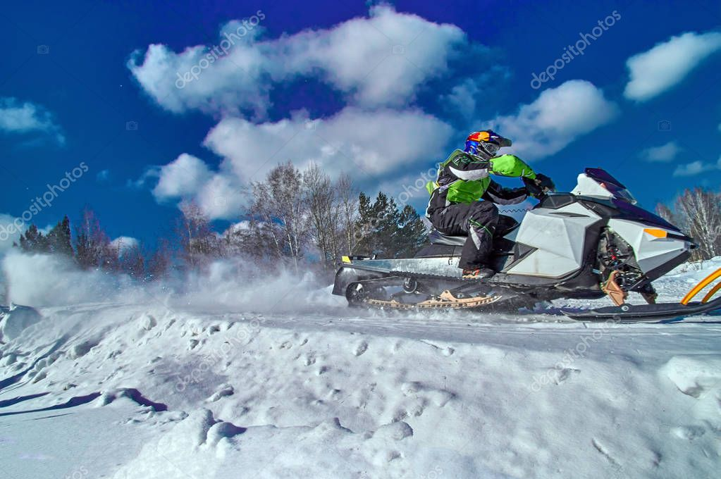 Sports snowmobile is riding at high speed. Extreme competitions on a sunny winter day. Concept quick movement. Side view.