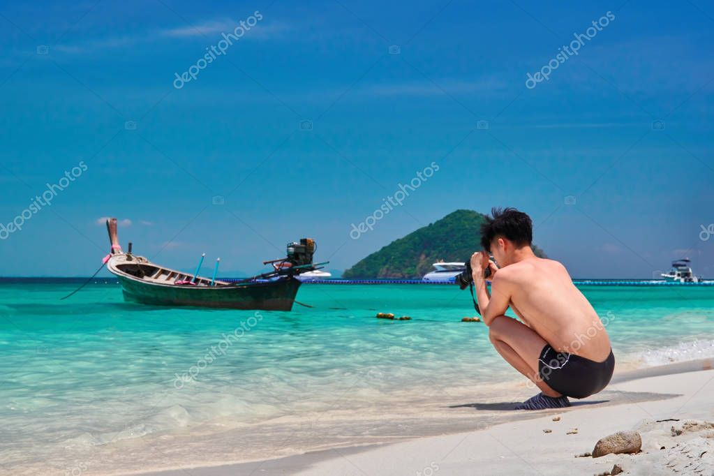 THAILAND, CORAL ISLAND, MARCH 19, 2018 - Beautiful young man looks at the screen of his camera. Tropical landscape with turquoise serene sea and blue sky.