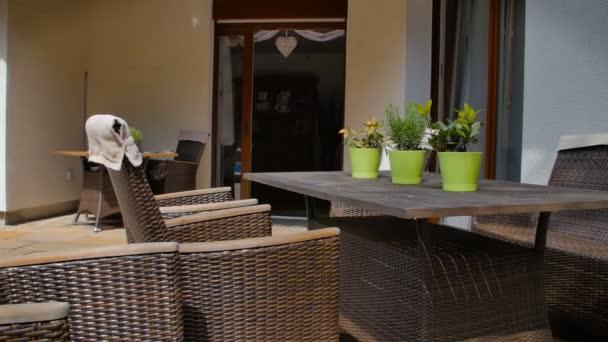 Terrasse eines mediterranen Gartens mit Korbmöbel