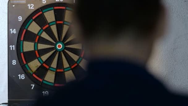 muž si hraje hru šipky, zaměření na cíl