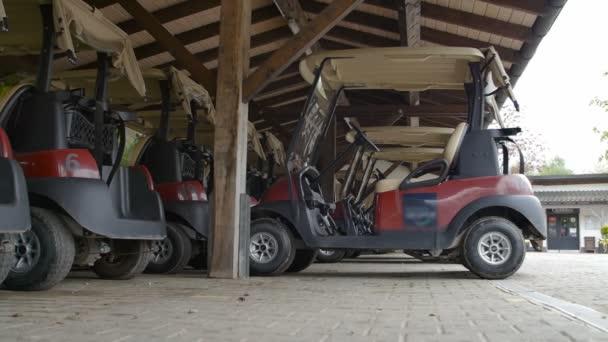 Golfové vozíky zaparkovaná v kryté dřevěné místo