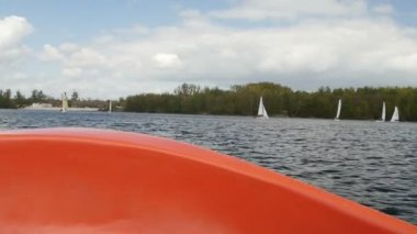 View from boat bow when fast moving over water with regatta in background