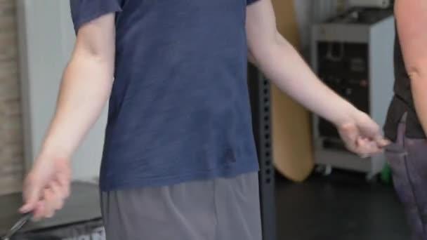 Sport a fitness cvičení. Zdravý atletický muž v modrém tričku skákání s skákacím lanem, cvičení uvnitř. Pohledný muž dělá skákání kardio cvičení.