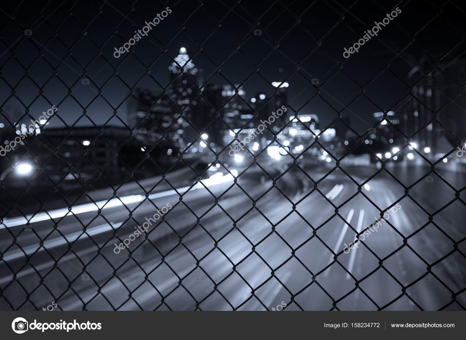 Night city skyline through the wire mesh fence — Stock Photo ...