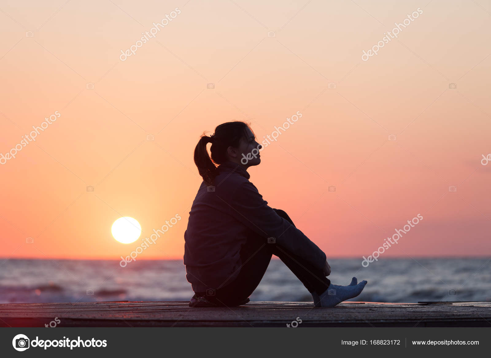 Lonely girl sitting on the sunrise beach — Stock Photo