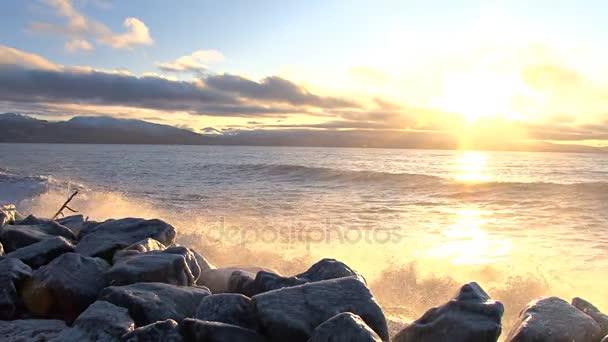 vlny na skalách při západu slunce