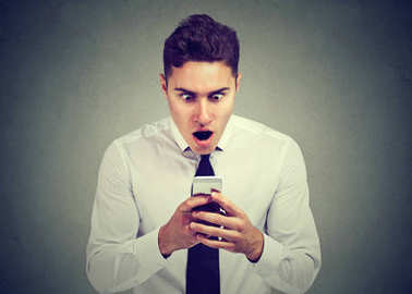 surprised man looking at phone seeing unexpected news or photos with wonder emotion on face