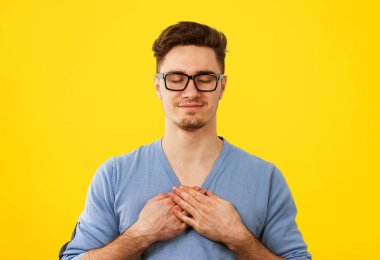 Faithful man with eyes  closed keeps hands on chest near heart, shows kindness