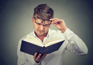 Frowning man having problems with reading