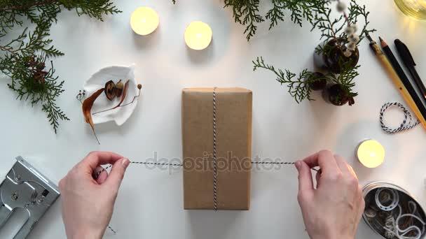 Dárková krabička v kraftový papír na bílém pozadí. Současnost zdobené přírodními dílů. Vánoční nebo novoroční koncept, pohled shora