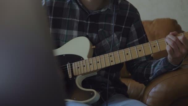 Mladý muž hraje na kytaru, nahrávání hudby doma