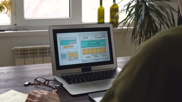 Webentwickler, der am Tisch sitzt und eine Skizze der zukünftigen Website erstellt. Arbeiten aus der Ferne vom Home Office.