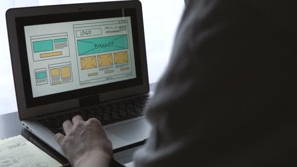 Webový vývojář, sedí u stolu, takže nástin budoucího webu. Práce vzdáleně z domácí kanceláře