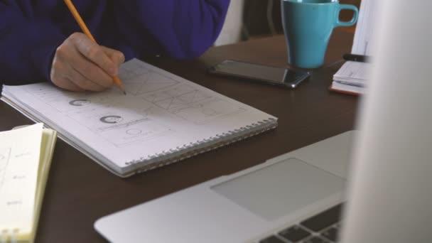 Vývojář aplikace nakreslí skici v poznámkovém bloku. Práce vzdáleně z domácí kanceláře