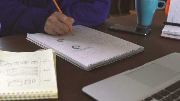 Der Anwendungsentwickler zeichnet Skizzen in ein Notizbuch. funktioniert von zu Hause aus