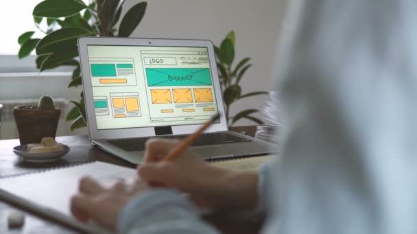 Freiberufler am Arbeitsplatz. Web-Entwickler macht Skizzen der Website in seinem Notizbuch, das von zu Hause aus arbeitet