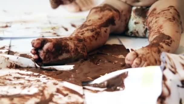 Baby malen mit Händen mit Schokolade