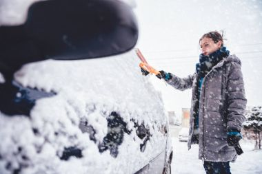woman cleaning car with Scraper