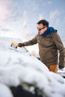 man cleaning snow covered car