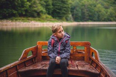 girl sitting in wooden boat