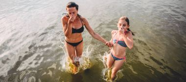 Mother and daughter jumping into water