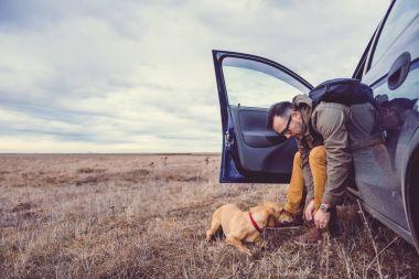 Hiker in car near dog