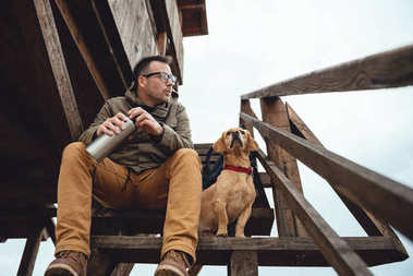 Hiker and dog sitting on stairs