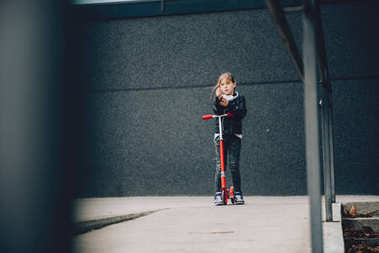 Girl driving red scooter