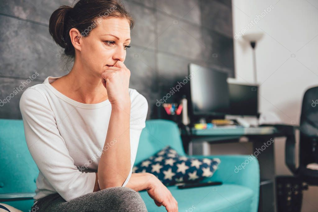Sad woman sitting on a sofa in the living room