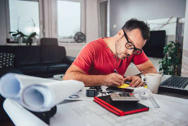 Man writing notes on memo pad on busy desk at home office